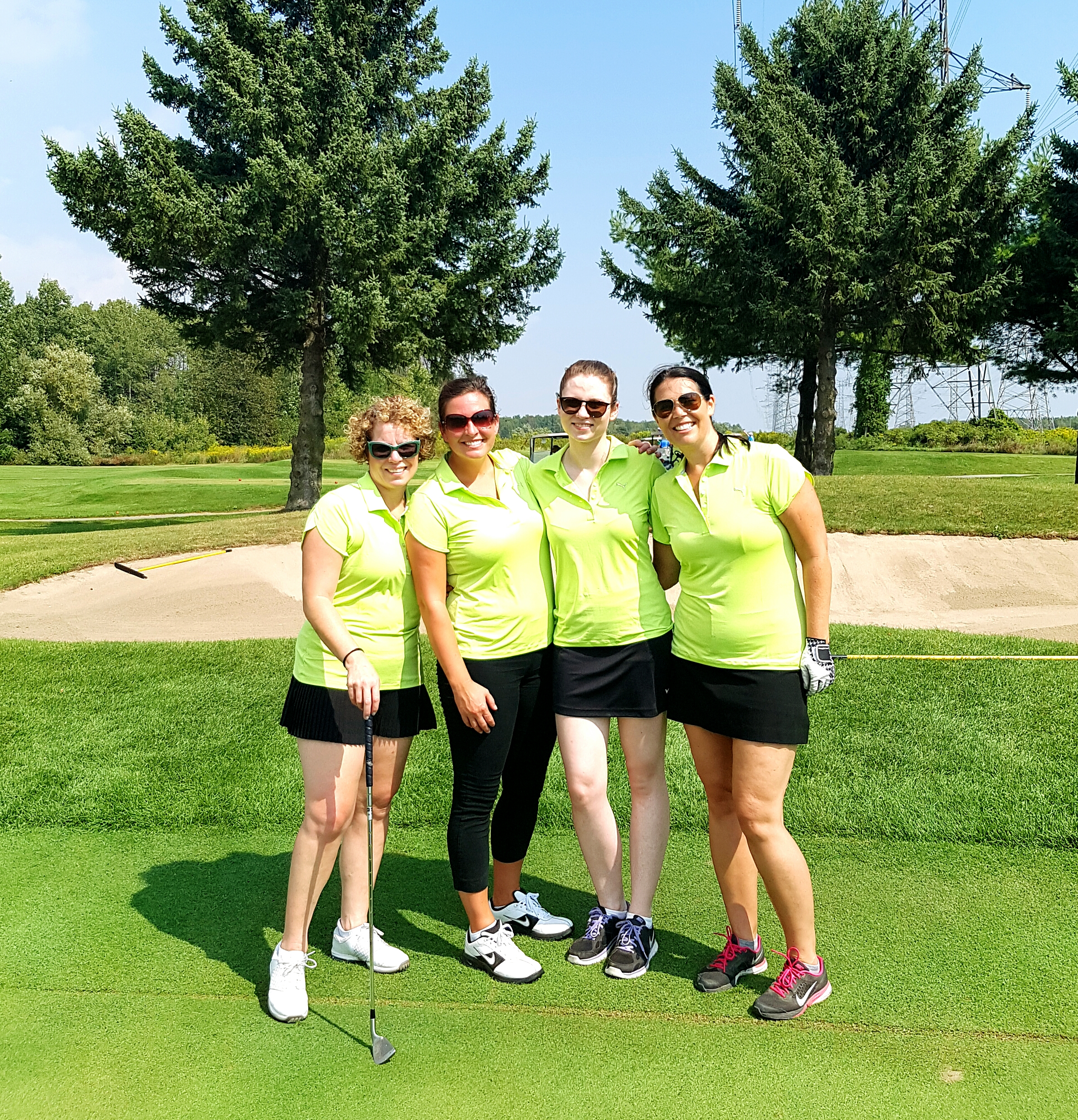 four smiling people standing on a golf course wearing bright green golf shirts