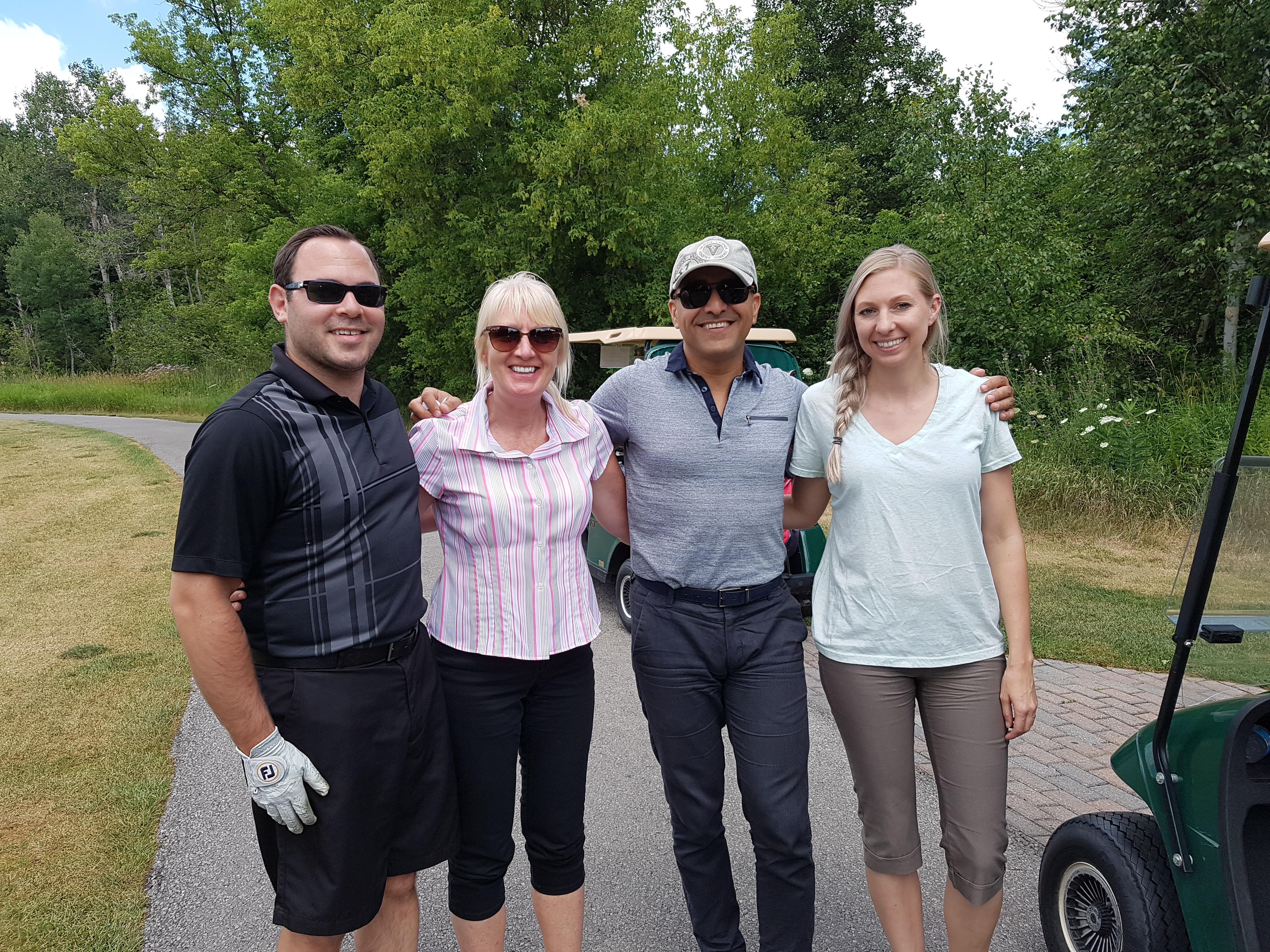 A group of four smiling people on a golf course