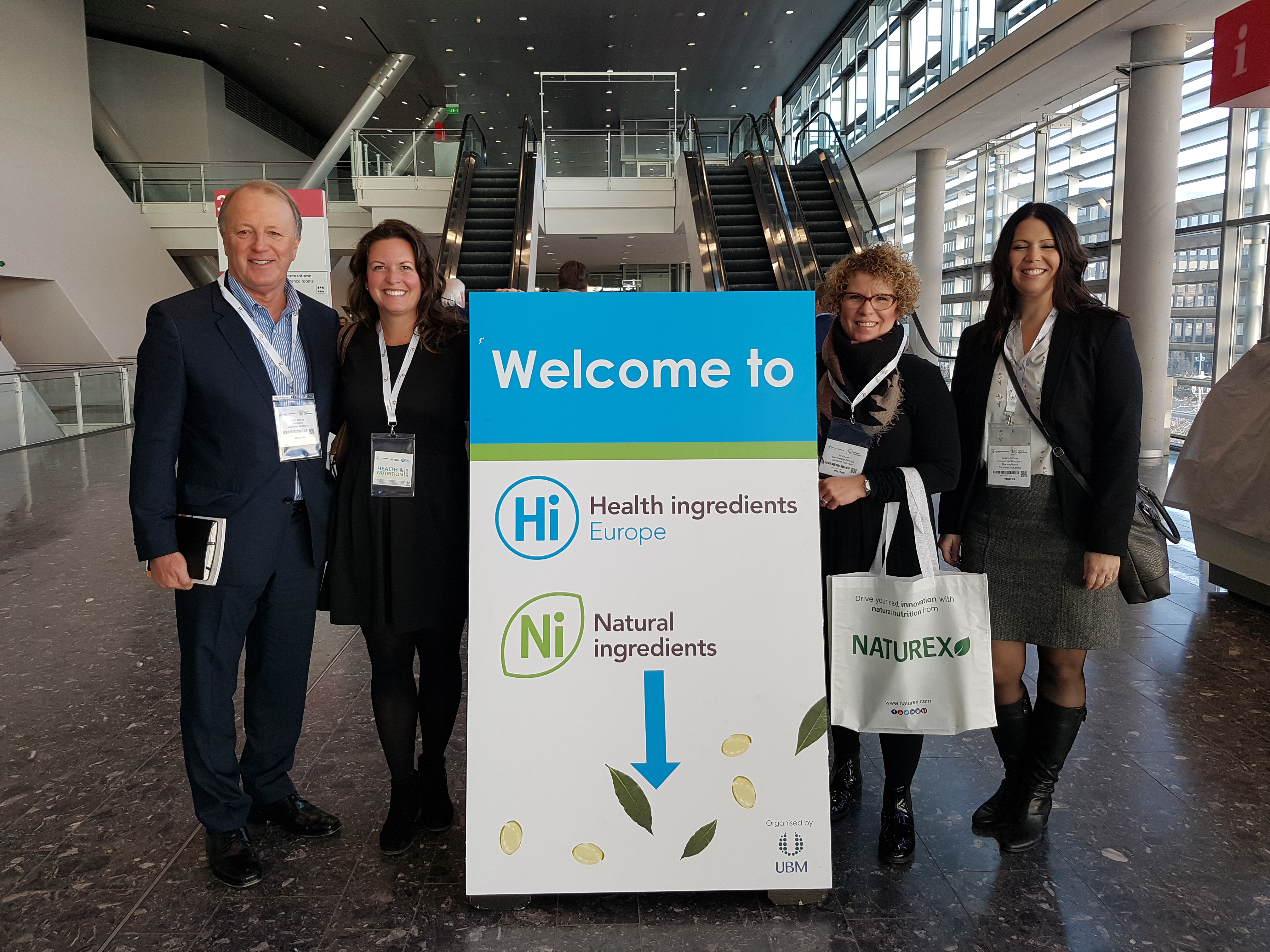 """Four people standing around a sign which says """"Welcome to Health Ingredients Europe"""""""