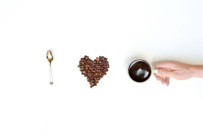 Spoon, fairtrade coffee beans in a heart shape, and a cup of coffee on a white background