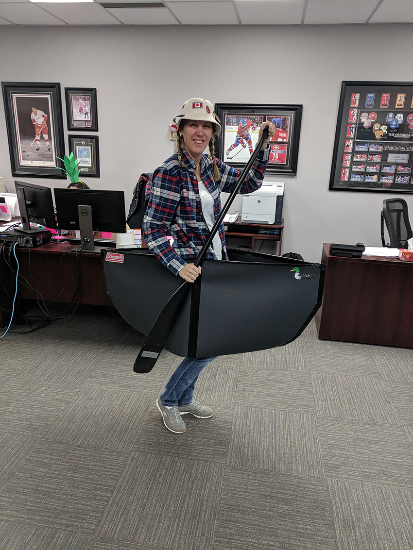 Kim as the winner of the best costume in her wearable canoe, a fishing hat, and a plaid shirt.