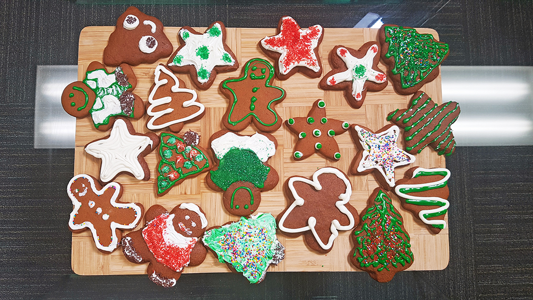 Gingerbread Cookies decorated with white and green icing and sprinkles, cut in the shape of gingerbread men, stars, and trees.