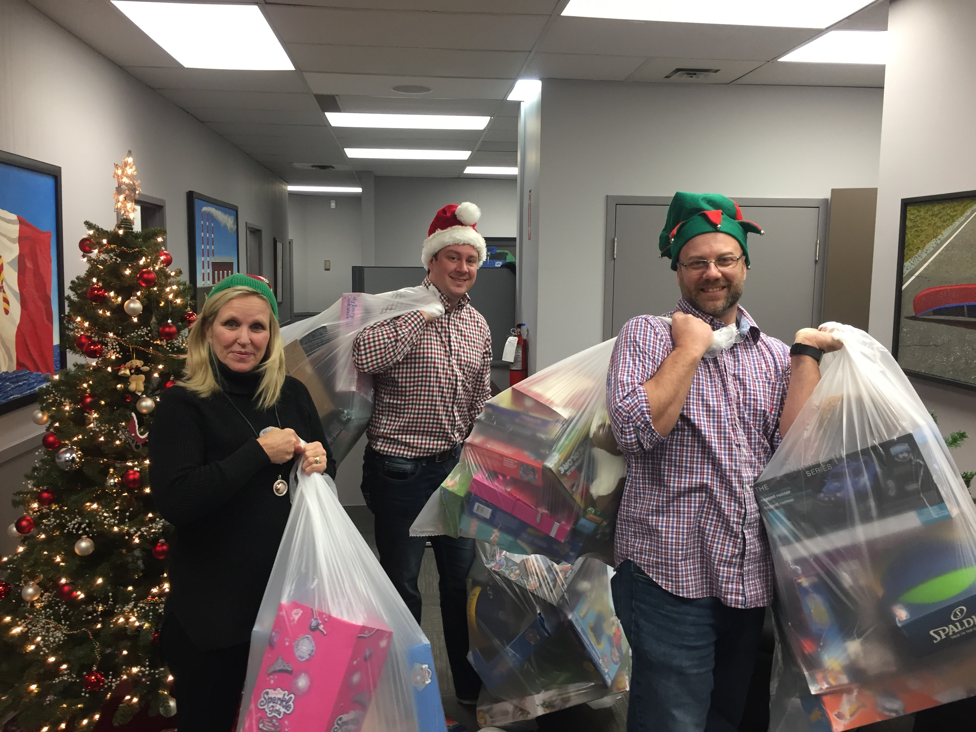 Two men and a woman wearing Christmas hats with bags full of toys from Cambrian's Christmas Toy drive