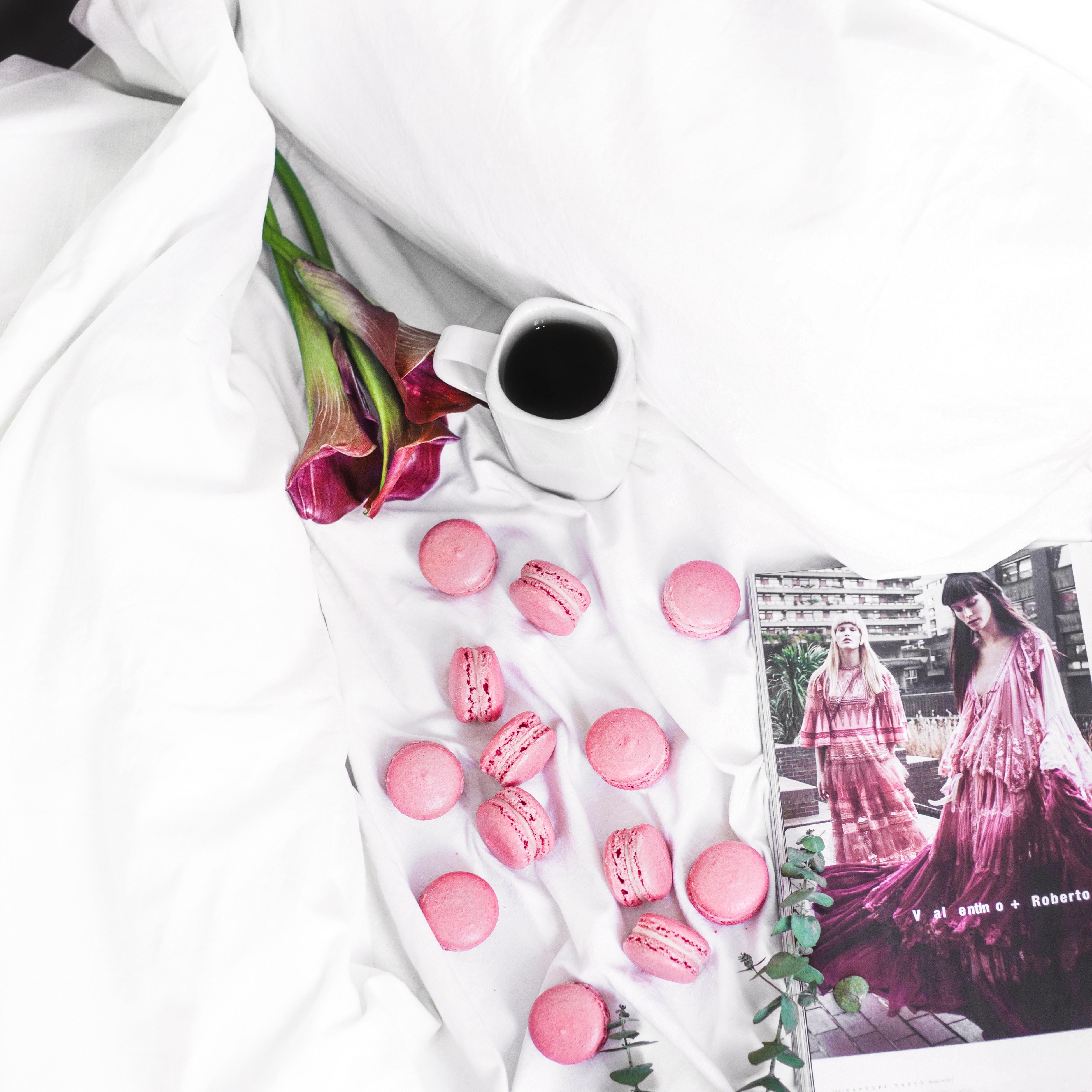 magazine, coffee, flowers, and some pink macarons on a marble counter