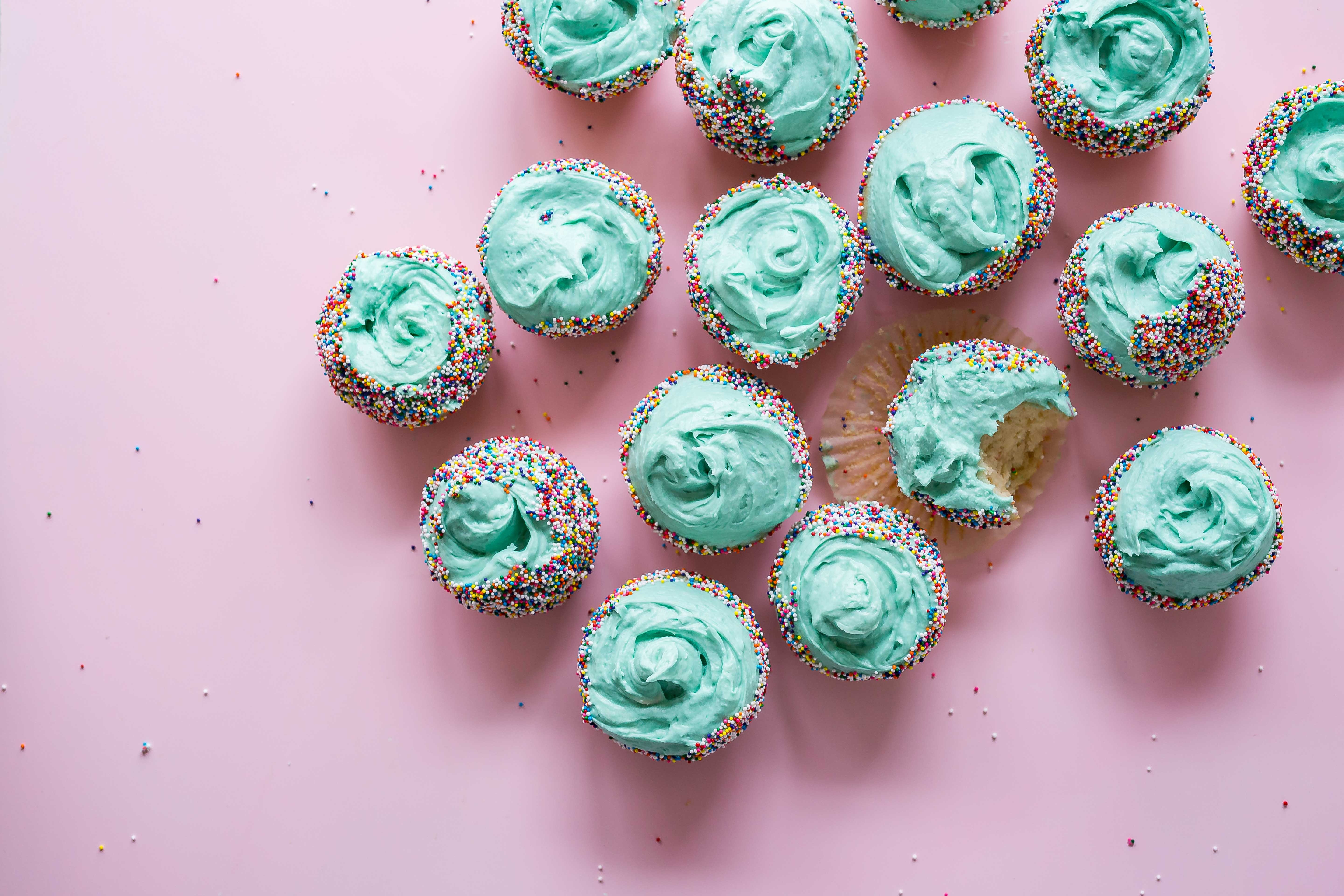 vibrant teal cupcakes, one with a bite out of it, on a soft pink background