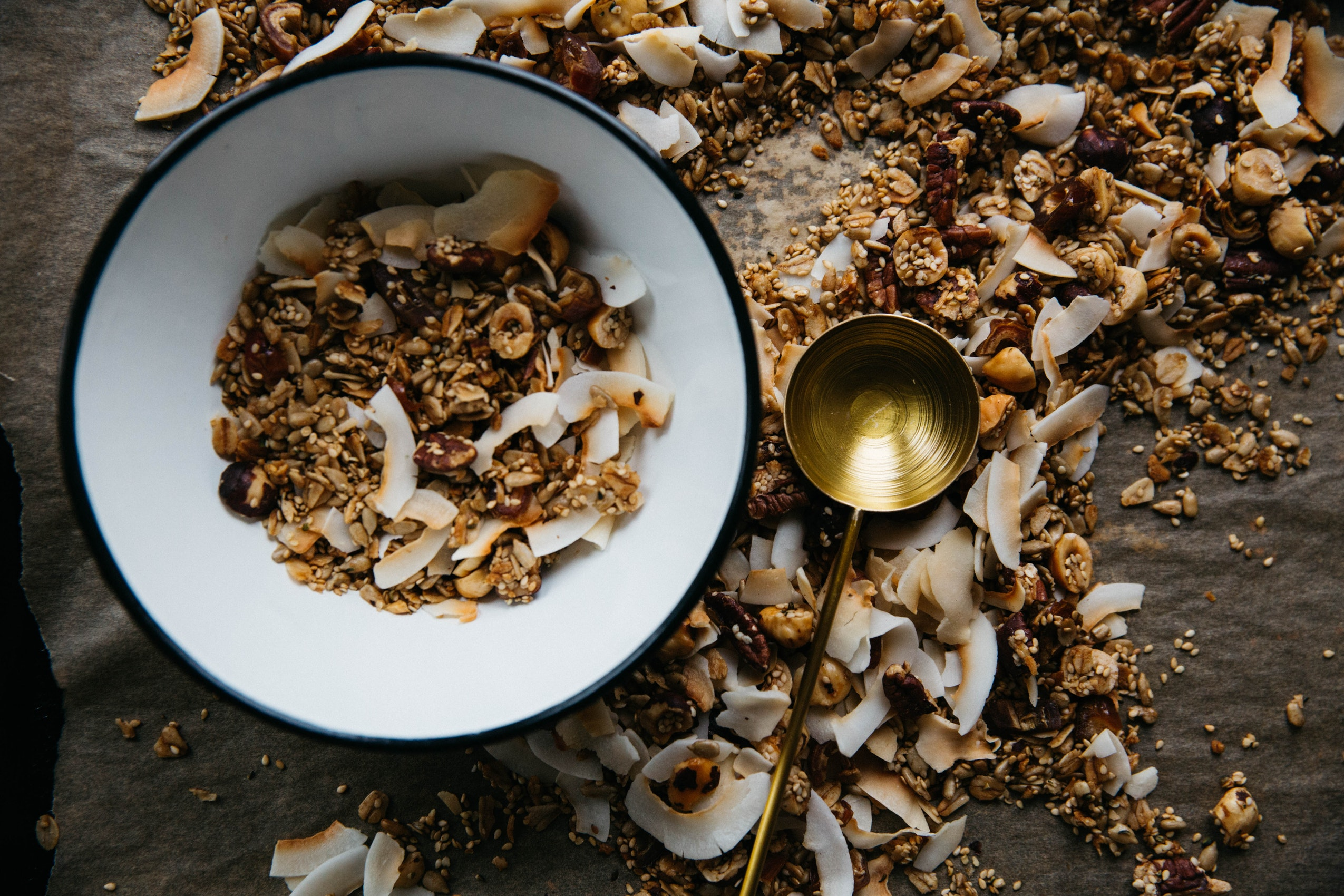 Coconut in a granola meal in a bnowl with a spoon next to it and granola and coconut shavings all over the table.