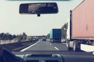View from the dashboard of a car. Two transport trucks are in the lane to the right of the car. Clear blue sky, straight highway in front.