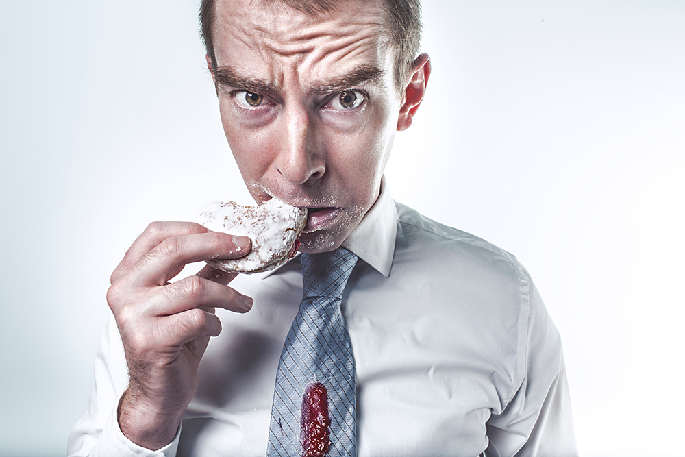 Shocked looking man eating a sugary snack