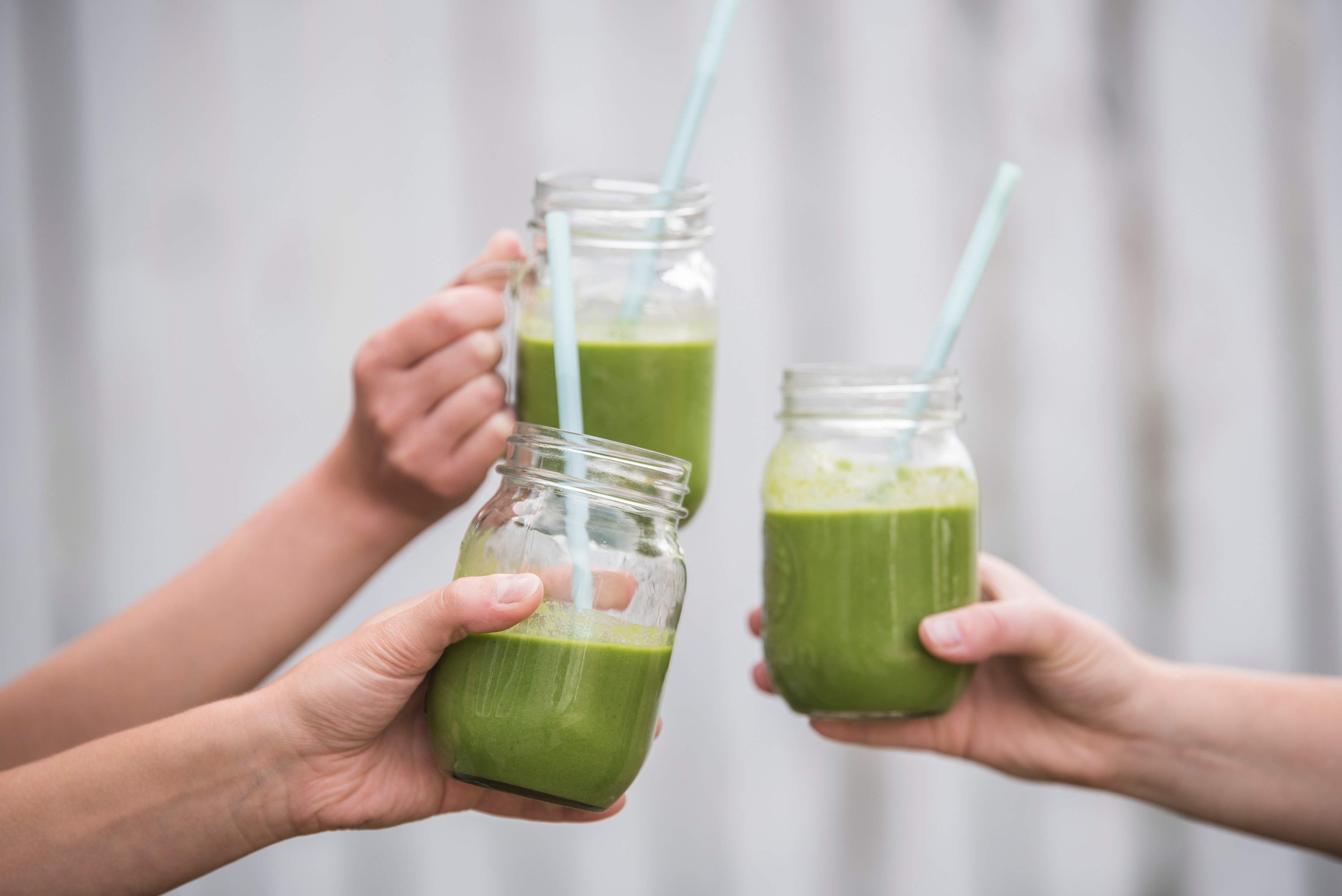 hands cheers-ing with green smoothie