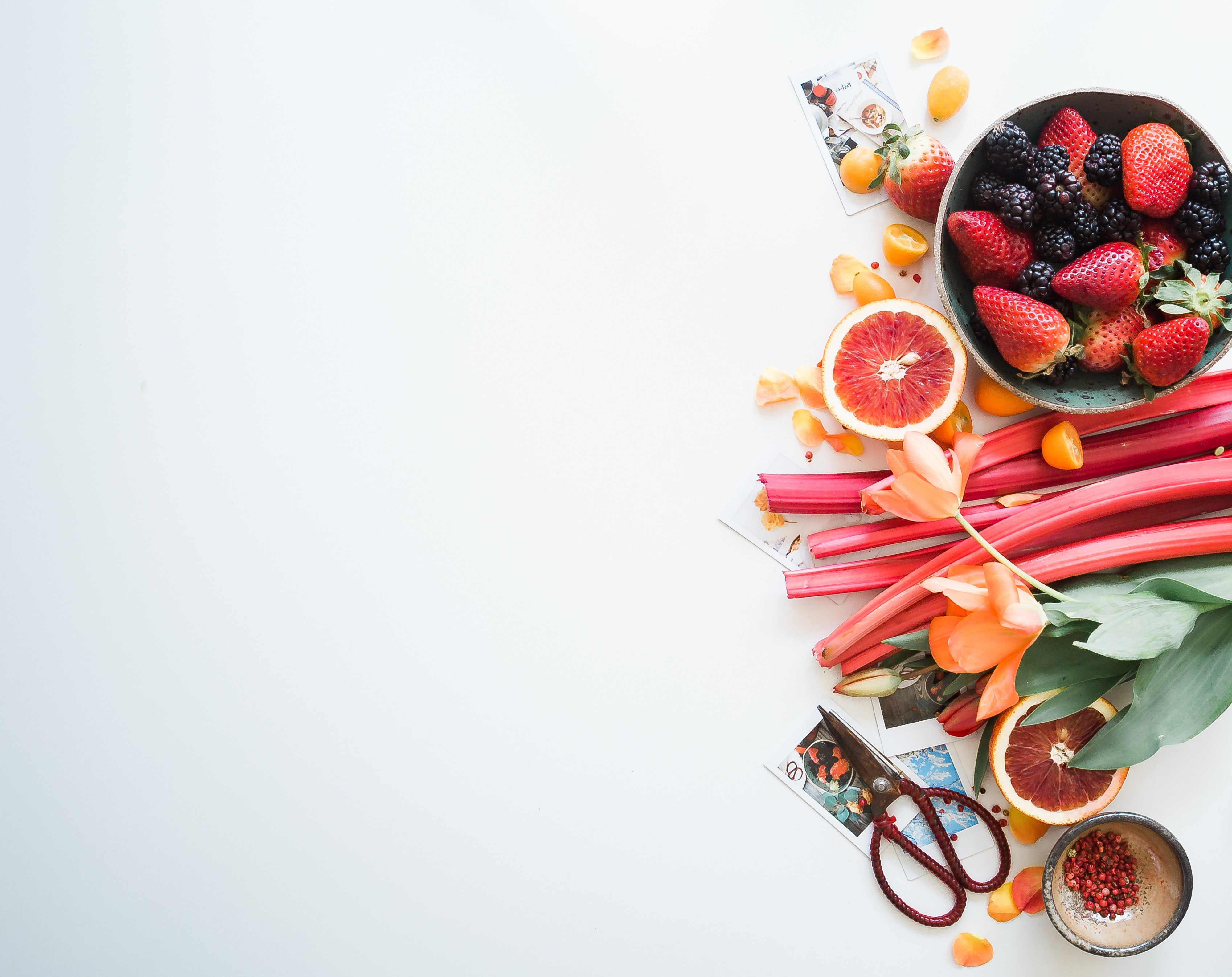 Rhubarb, a bowl of berries, two halves of blood oranges and various other fruits on a white background.