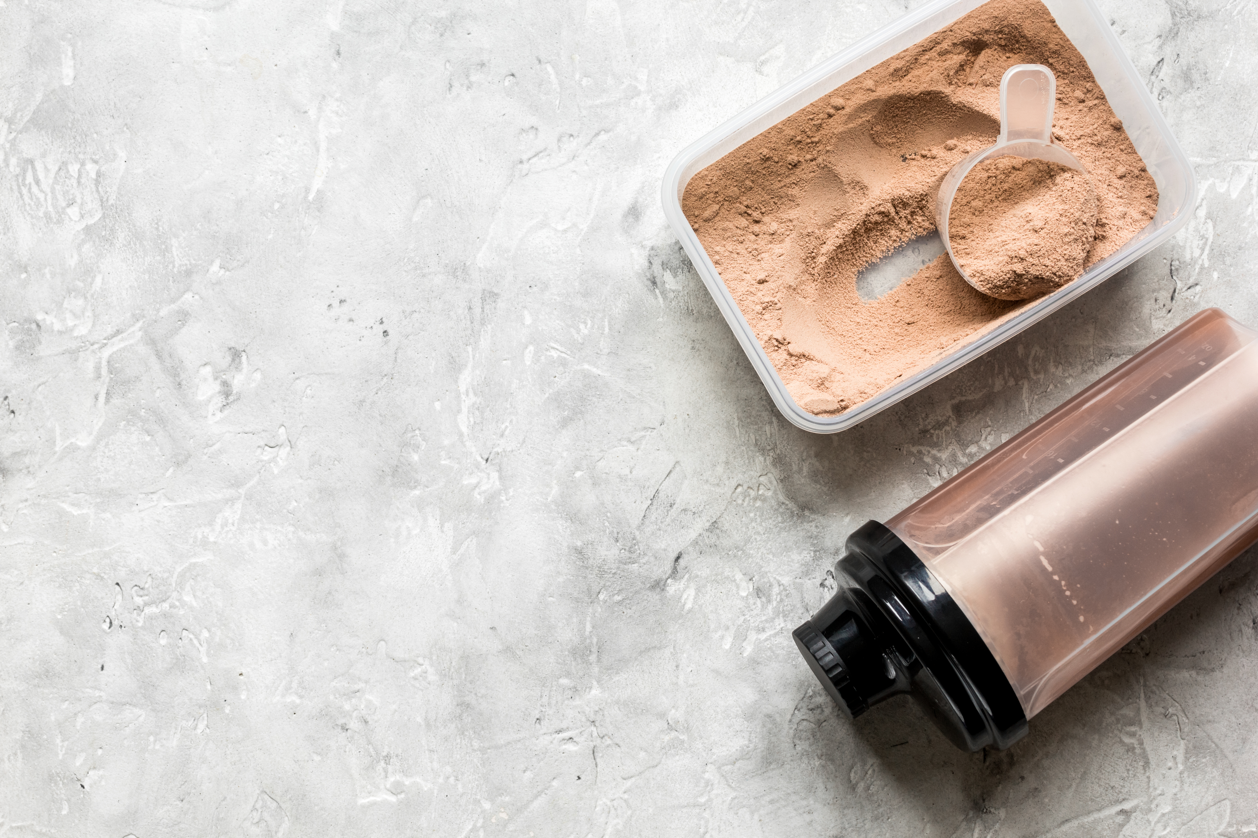 A protein shaker beside a plastic container with protein powder and a scoop in it.