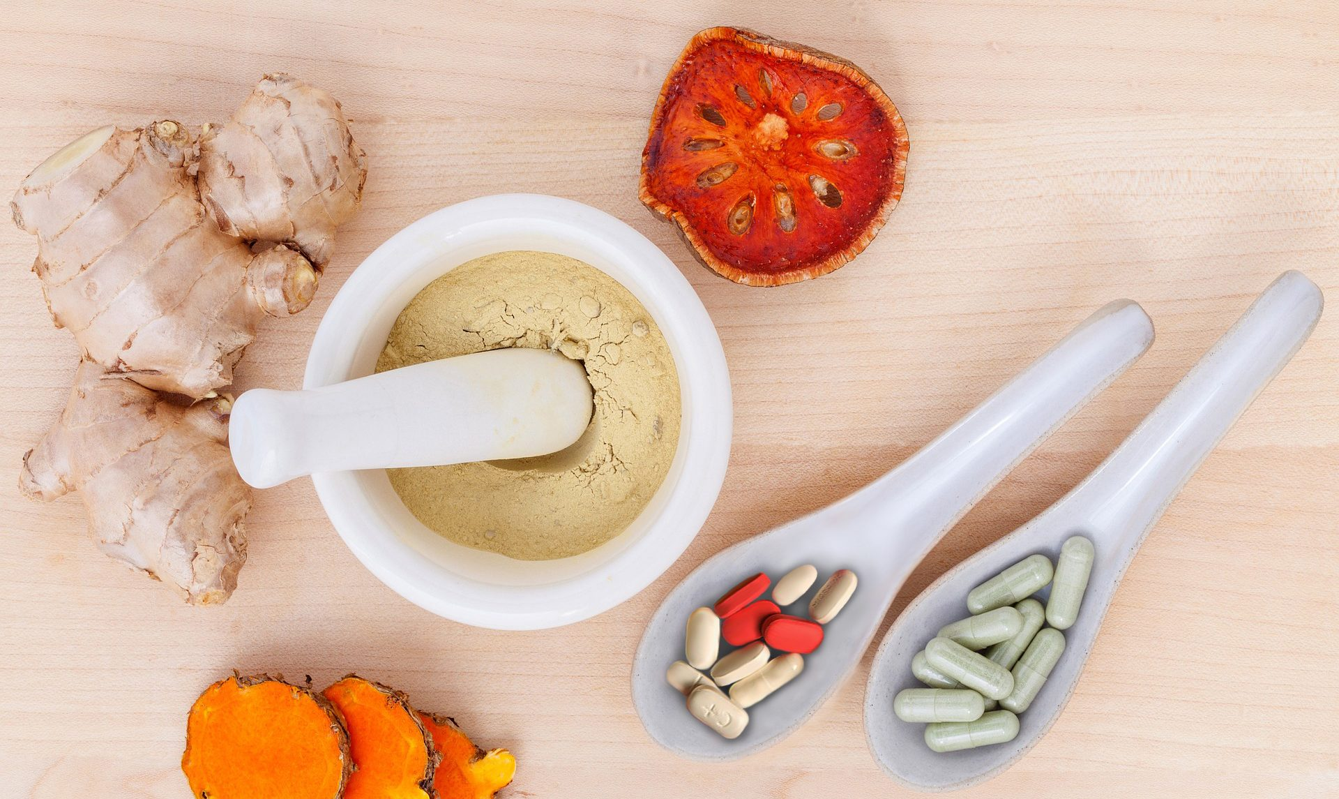 image of pills, supplements, ginger, and some other health ingredients on a wooden background