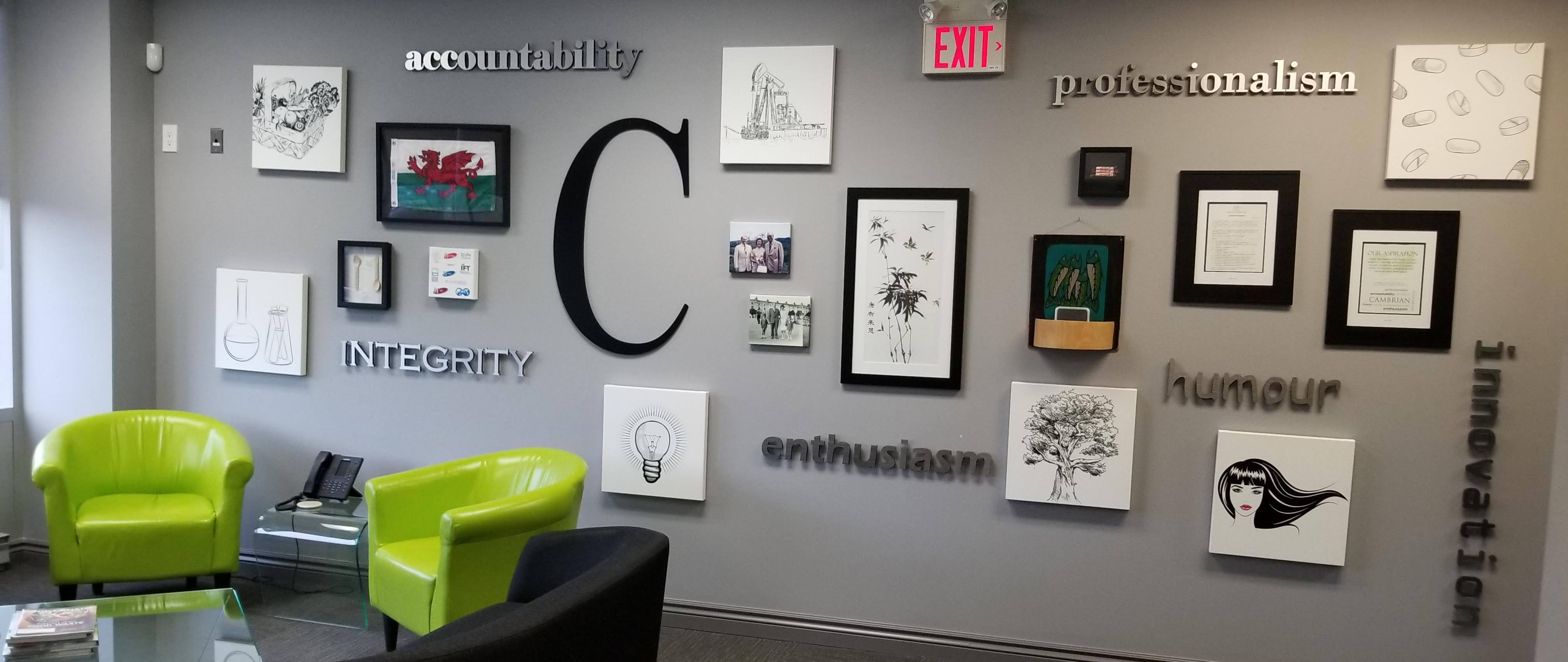 "Cambrian LK Lounge wall which features a decorative wall. On the wall the words ""accountability"" ""integrity"" ""professionalism"" ""enthusiasm"" ""humour"" and ""innovation"" appear among images representing the various divisions of Cambrian."