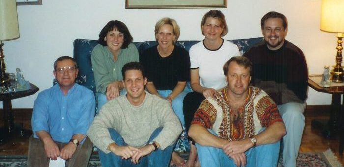 Three women and a man are seated on a couch. Three men sit on the floor in front of them. All of them are smiling at the camera.