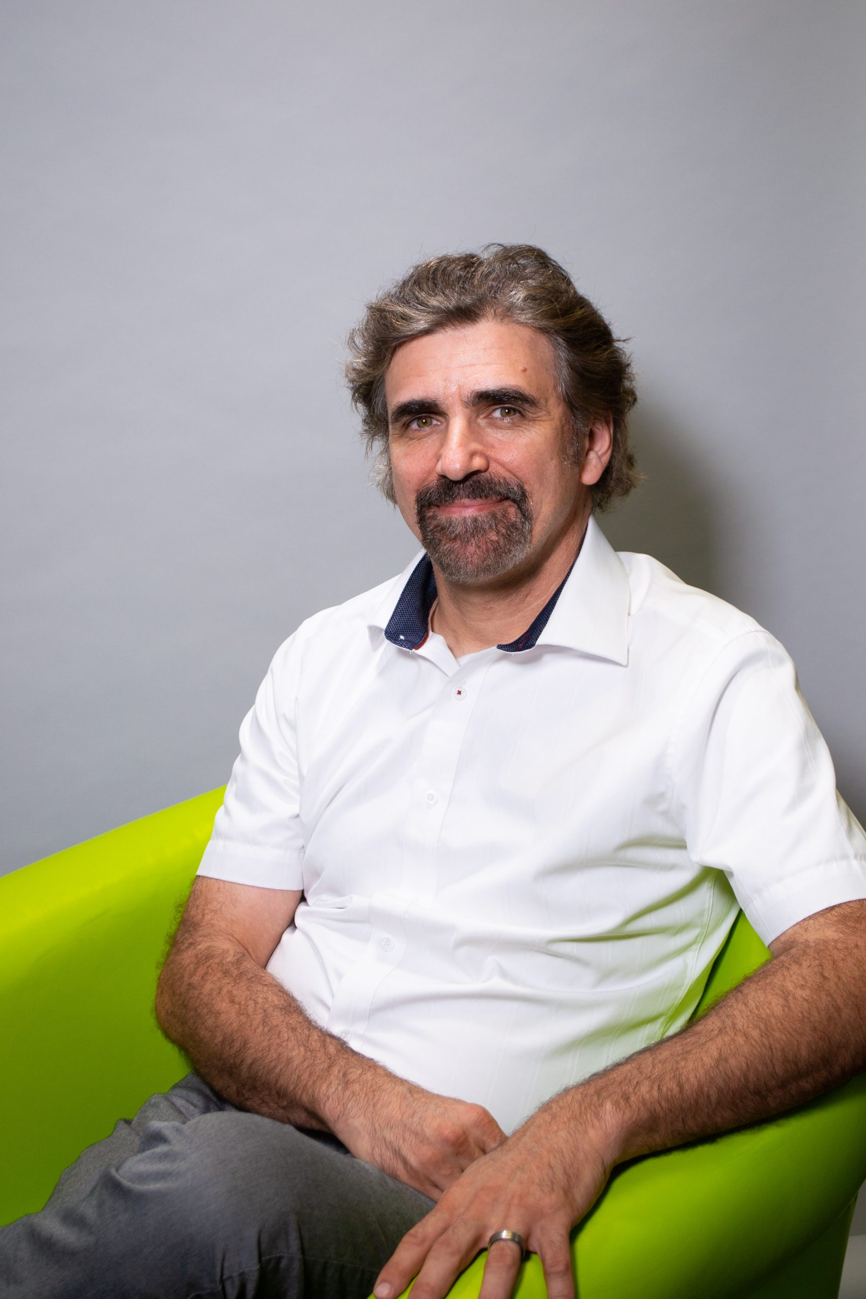 Tony Csaba sitting in a green chair in front of a grey background, smiling at the camera