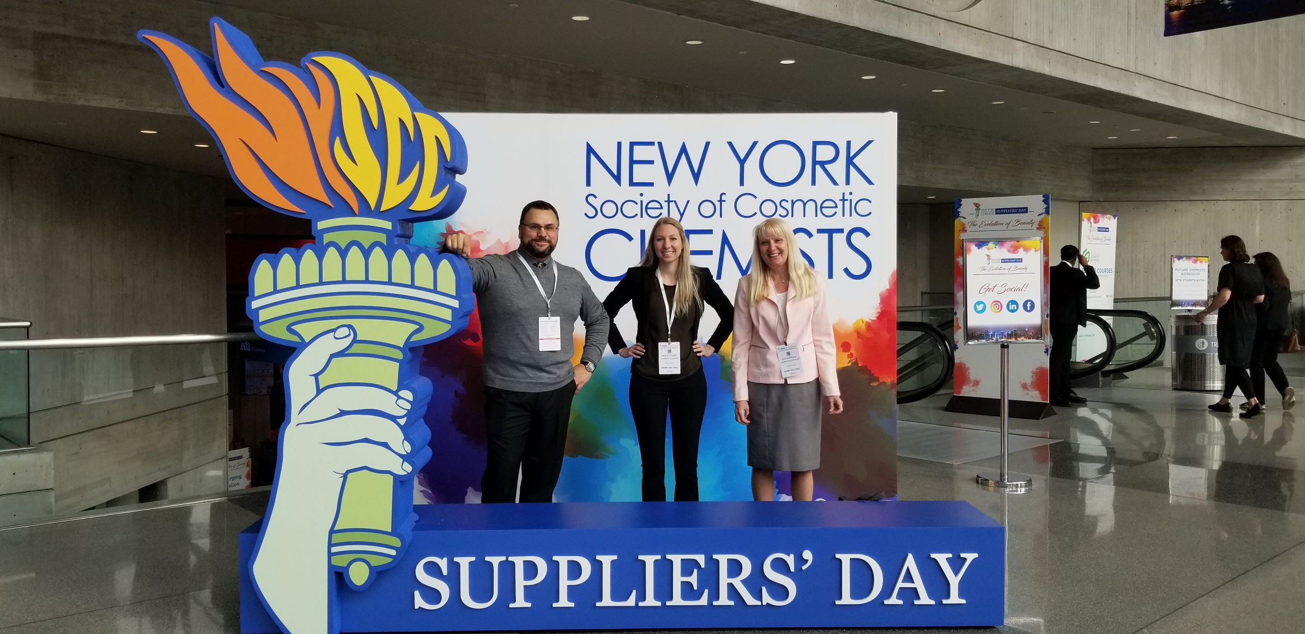 "A man and two women stand in a display which has a green hand holding a torch. The display says ""New York Society of Cosmetic Chemists Suppliers' Day"""