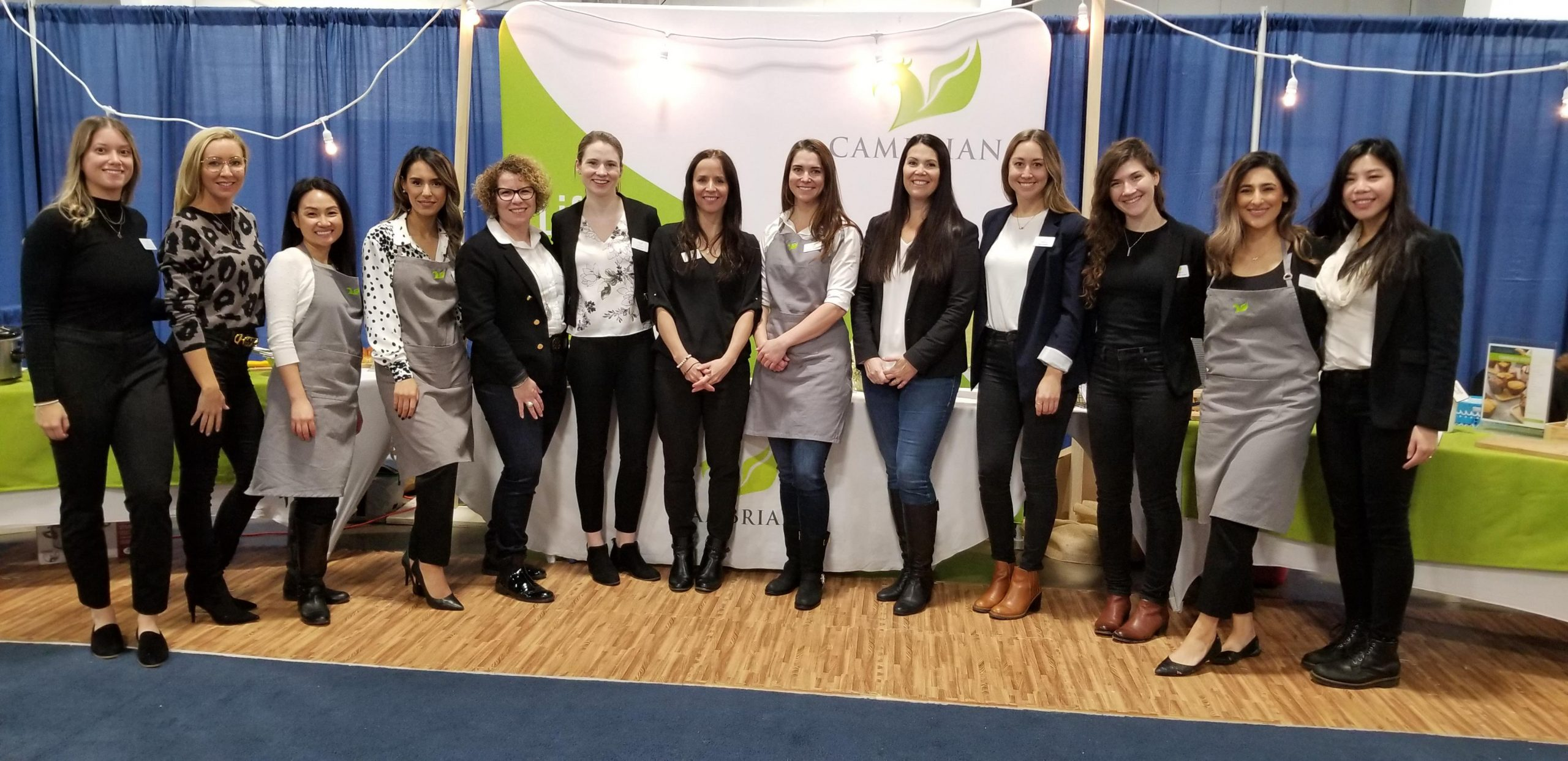 A group of 13women stand, smiling, in front of a Cambrian trade show booth. Most are wearing black blazers, four are wearing grey aprons.